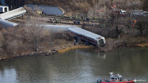 Emergency workers gather at the site of a Metro-North train derailment in the Bronx borough of New York. At least four people were killed and 63 injured, including 11 critically, when the suburban train derailed, with at least five cars from the Metro-...