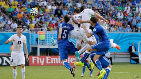 Uruguay's Diego Godin, second right, heads the ball to score his side's first goal during the group D World Cup soccer match between Italy and Uruguay at the Arena das Dunas in Natal, Brazil.