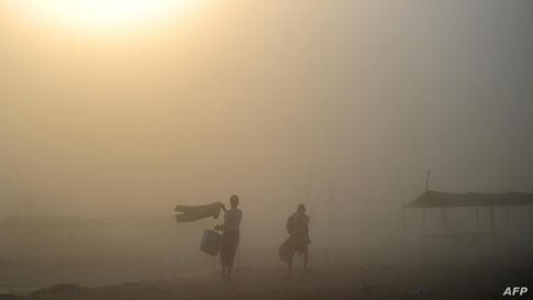 Indian Hindu devotees walk through a dust storm after taking a holy dip at the Sangam, the confluence of the rivers Ganges, Yamuna and mythical Saraswati, in Allahabad.