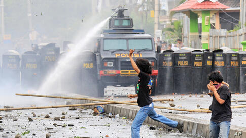 Indonesian students react as a police water cannon truck sprays water to disperse a rally commemorating the International Anti-Corruption Day that turned violent in Makassar, South Sulawesi.