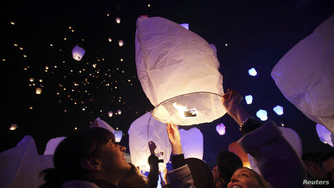 """A participant releases a sky lantern during the """"Kapulica & Lanterns"""" event in Zagreb, Croatia, Dec. 23, 2013. The event, organized by contemporary artist Kresimir Tadija Kapulica as part of the ArtOmat Fair ahead of Christmas, involves people releasin..."""