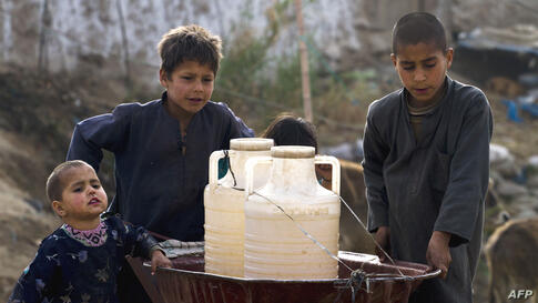 Pakistani boys transport water containers on a wheelbarrow after collecting water from a hand-pump on the outskirts of Islamabad, March, 21, 2012.  (AP)