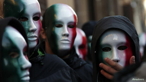 """Members of Casapound far-right organization wear masks in the colors of the Italian flag before a demonstration organized by """"People from pitchfork movement"""" to protest against economic insecurity and the government in downtown Rome."""