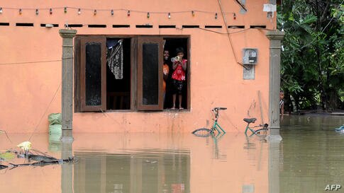 Sri Lankan residents look out of the window of their home at floodwaters in Matugama, some 64 kms south of Colombo on June 3, 2014 after heavy monsoon rains caused havoc in the western, southern and central regions of the island.