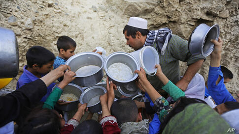 Afghan villagers flock around free food donated by other villagers as they prepare to break their fast during the holy month of Ramadan in Kabul.