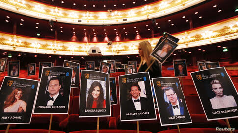 A production staff member places position markers representing guests ahead of the BAFTA awards at the Royal Opera House in central London. The BAFTA film awards will take place on Feb. 16, 2014.