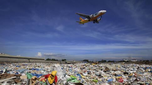 An aircraft flies overhead as a person rummages for recyclables at a garbage dumpsite in Paranaque city, metro Manila, Philippines.