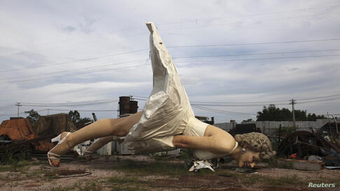 A giant statue of U.S. actress Marilyn Monroe is seen at the dump site of a garbage-collecting company in Guigang, Guangxi Zhuang Autonomous Region, China, June 18, 2014. The eight-meter-tall stainless steel statue, which weighs about eight tons, was m...