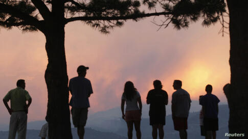People watch a giant smoke plume rising from the Waldo Canyon Fire during sunset, west of Colorado Springs