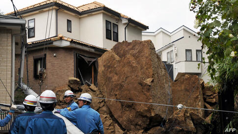 """A house and an electric pole smashed by large rocks from a collapsed slope caused by heavy rain in Kamakura, suburban Tokyo. At least 17 people died as Typhoon Wipha, the """"strongest in 10 years"""", passed close to Tokyo, causing landslides that swallowed..."""
