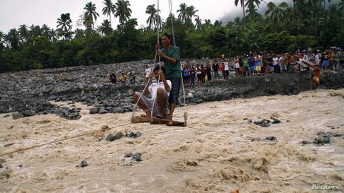 Residents use an improvised cable car to reach relief goods across a rampaging river after a non-stop downpour spawned by a low pressure area flooded New Bataan town, Compostela province, southern Philippines, Jan. 14, 2014.