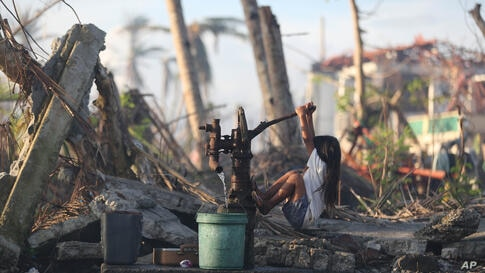A young typhoon survivor fetches water from a hand pump at typhoon-ravaged Tolosa town, Leyte province, central Philippines.
