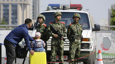 Armed paramilitary police officers stand guard at Beijing Railway Station. An assailant stabbed six people at a railway station in the southern Chinese city of Guangzhou, police and state media said.
