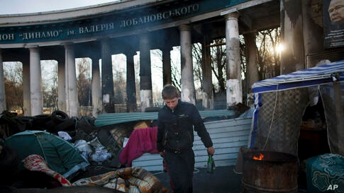 A man clears bottles at a barricade near the entrance to the stadium of Dynamo Kyiv soccer club in Ukraine.