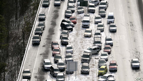 Abandoned cars on I-75 headed northbound near the Chattahoochee River overpass are piled up in the median of the ice-covered interstate after a winter snow storm in Atlanta, Georgia, USA. Georgia Gov. Nathan Deal said that the National Guard was sendin...