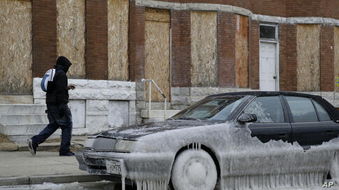 A man walks past a car partially covered in ice in Baltimore, Maryland, where temperatures continue to remain well below freezing. An arctic blast eased its grip on much of the U.S., with winds calming and the weather warming slightly a day after tempe...