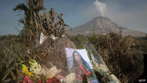 Flowers and a portrait of a victim, killed during the eruption of Mt. Sinabung volcano, are left by relatives on a hill in Karo district with the volcano in the background. The volcanic eruption killed 15 people in a weekend and hot ash and rocks shot ...