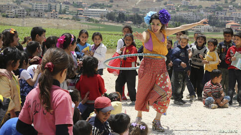 Members of Clowns Without Borders entertain Syrian refugee children in Jab Janine, West Bekaa, Lebanon, June 2, 2014. Clowns Without Borders is an international non-profit organization that uses laughter to relieve suffering among children in refugee c...