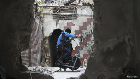 A Free Syrian Army fighter exercises as he is seen through a hole in a wall in the Seif El Dawla neighbourhood in Aleppo, Syria.
