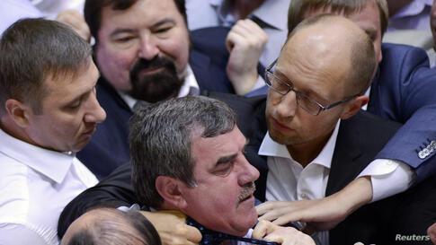 Opposition leader Arseny Yatsenyuk (top R) holds the tie of a deputy from the pro-presidential Party of the Regions (C), as opposition deputies attempt to disrupt a parliament session in Kyiv, Ukraine.