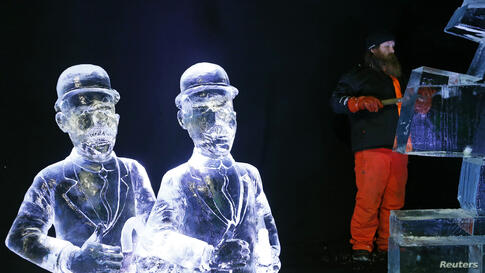 Sculptor Juuso Partanen of Finland carves a sculpture near other sculptures based on characters of comic strips at the Brussels Ice Magic Festival, Belgium.