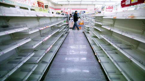 A man shops in a convenience store on Tuesday, where shelves on food aisles are left empty in Ofunato, northern Japan. (AP)