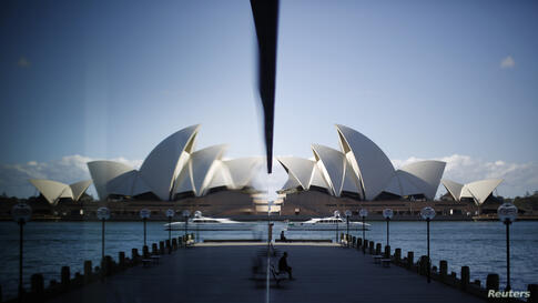 The Sydney Opera House is reflected in a harborside hotel window in The Rocks district of Sydney, Australia.