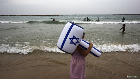 A girl holding to an inflatable hammer in the color of the Israeli flag stands on a beach at Tel Aviv during an aerial show as part of celebrations for Israel's Independence Day to mark the 66th anniversary of the creation of the state.