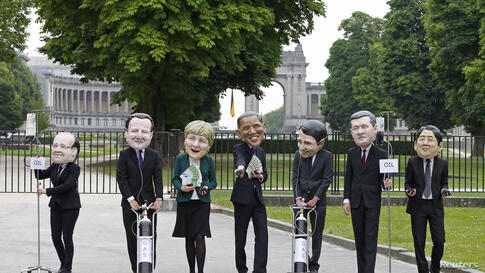 Oxfam's activists wear masks depicting leaders of the countries members of the G7, (L-R) French President Francois Hollande, British Prime Minister David Cameron, German Chancellor Angela Merkel, U.S. President Barack Obama, Italian Prime Minister Matt...