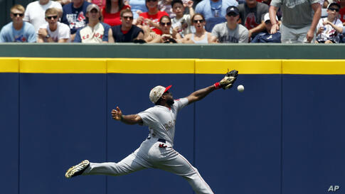 Boston Red Sox outfielder Jackie Bradley tries to reach a 2-RBI double hit over his head by Atlanta Braves' Justin Upton during the third inning of a baseball game in Atlanta, Georgia, USA, May 26, 2014.