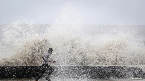 A school boy runs to get drenched in a large wave during high tide at a sea front in Mumbai.
