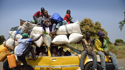 Christian people crowd a taxi on a road 55km north of Bangui, Central African Republic, as they are on their way to the capital where they expect to sell some products on the market.