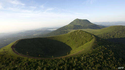 A picture shows the Chaine des Puys, a volcanic chain of 80 volcanoes over a distance of 32 km, with the Puy de Dome (top) and the Puy de Pariou (bottom) near Clermont-Ferrand. The World Heritage Committee will decide on June 21, 2014 whether the Chain...