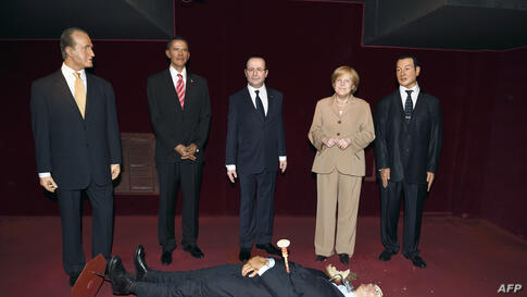 The wax statue representing Russian President Valadimir Putin, whose head was damaged by an activist of the Femen feminist group, lies on the floor next to wax statues of Spain's King Juan Carlos (L), U.S. President Barack Obama (2ndL), French Presiden...