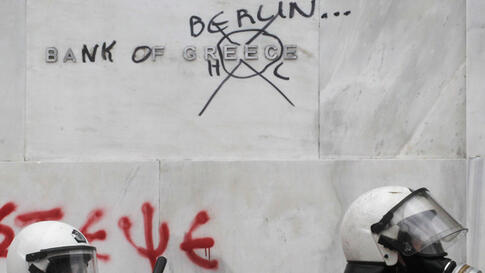 Riot police pass outside the main building of the bank of Greece during clashes in Athens, February 10, 2012. (AP)
