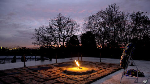 The eternal flame flickers in the early morning light at the grave of John F. Kennedy at Arlington National Cemetery on the 50th anniversary of Kennedy's death.