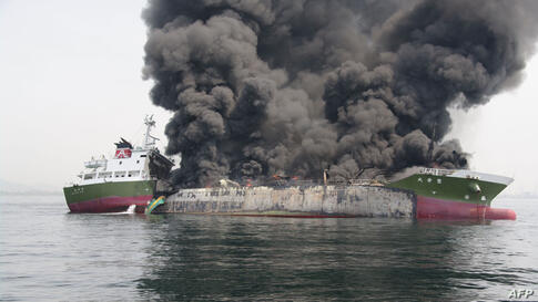 This handout picture taken and released by Japan's Coast Guard shows black smoke rising from a 998-ton oil tanker off the coast of Hyogo prefecture, around 450 kilometers (280 miles) west of Tokyo.
