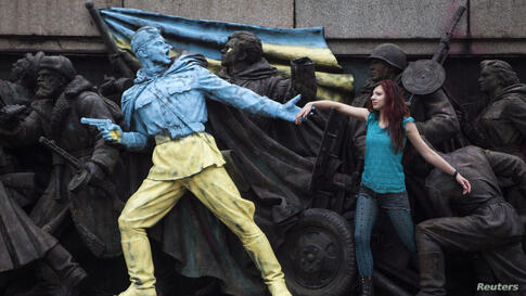 A woman poses for a picture with the figures of Soviet soldiers at the base of the Soviet Army monument, parts of which have been painted in the colors of the Ukranian flag by an unknown person in Sofia, Bulgaria, Feb. 23, 2014.