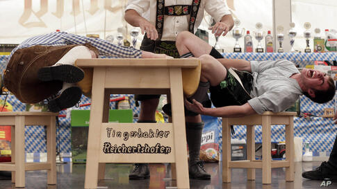 A judge watches the leather ring held by two competitors with their middle fingers at the Alps Finger Wrestling championships in Reichertshofen, southern Germany. Competitors battle for the title in this traditional rural sport where the winner has to ...