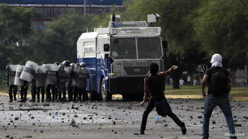 A student throws a rock toward riot policemen during a protest outside the National Autonomous University of Honduras in Tegucigalpa, Nov. 26, 2013. Clashes erupted between student demonstrators and police in the Honduran capital after conservative rul...