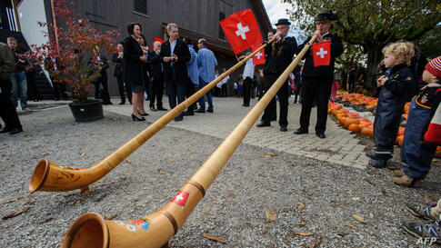 Finnish President Sauli Niinistoe (2nd L) and his wife Jenni Haukio (L) look at two men blowing into Swiss horns during a visit to a pedagogic farm in Seegraben, Switzerland.