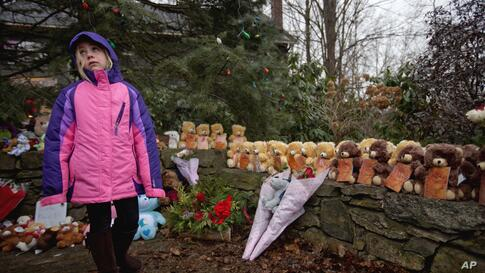 Ava Staiti, 7, of New Milford, Conn., looks up at her mother Emily Staiti, not pictured, while visiting a sidewalk memorial with 26 teddy bears, each representing a victim of the Sandy Hook Elementary School shooting, December 16, 2012, in Newtown, Con...