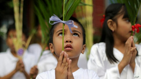 A Filipino boy participates in Palm Sunday rites outside the Holy Family Parish Church in Quezon city, north of Manila, Philippines.