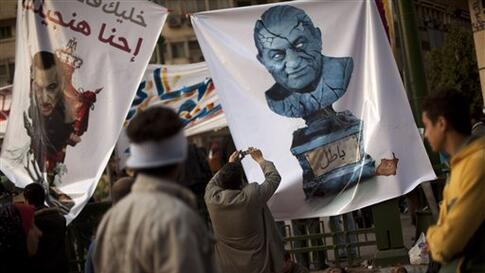 Anti-government protestors stand next to posters with cartoons of President Hosni Mubarak at Tahrir square in Cairo, Egypt, Wednesday, Feb. 9, 2011. Protesters appear to have settled in for a long standoff, turning Tahrir Square into a makeshift village w