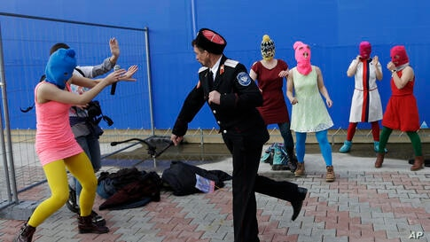 A Cossack militiaman attacks Nadezhda Tolokonnikova and a photographer as she and fellow members of the punk group Pussy Riot stage a protest performance in Sochi, Russia.