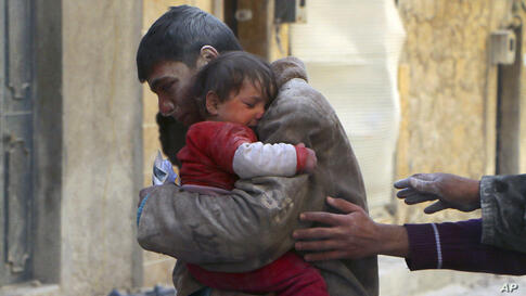A boy holds his baby sister, who survived what activists say was an airstrike by forces loyal to Syrian President Bashar al-Assad in Masaken Hanano in Aleppo.