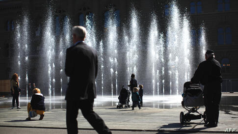 People watch a water fountain on the Swiss Federal square in Bern, Switzerland March 21, 2012. World Water Day, which is celebrated on March 22, aims to focus on water and food security. (Reuters)