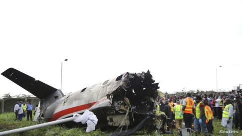 Rescue workers stand near the tail of a plane at the site of a crash near the Lagos international airport, Nigeria. Fifteen people were killed when an Embraer passenger plane crashed shortly after take-off just outside the airport's domestic terminal, ...