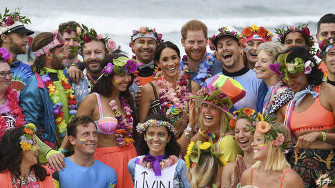 """Britain's Prince Harry (C-R) and his wife Meghan, the Duchess of Sussex (C-L) pose during a """"Fluro Friday"""" session run by OneWave, a local surfing community group who raise awareness for mental health and wellbeing, at Bondi Beach in Sydney"""