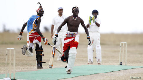 Sonyanga Olengais (C), captain of the Maasai Cricket Warriors, and his teammate Thomas Takare run between the wickets during their Twenty20 cricket match against the Ambassadors of Cricket from India, in Ol Pejeta conservancy in Laikipia National Park,...